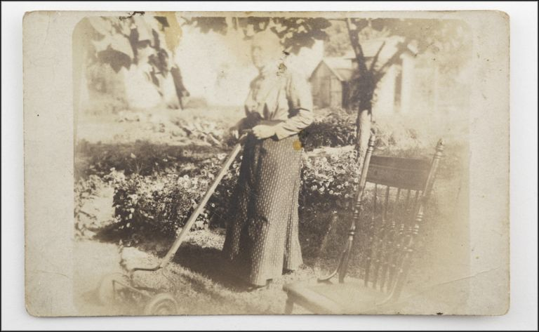 Real photo postcard outdoor portrait of a dignified matron named Mrs. Jones posing with a manual push lawnmower. Photography.