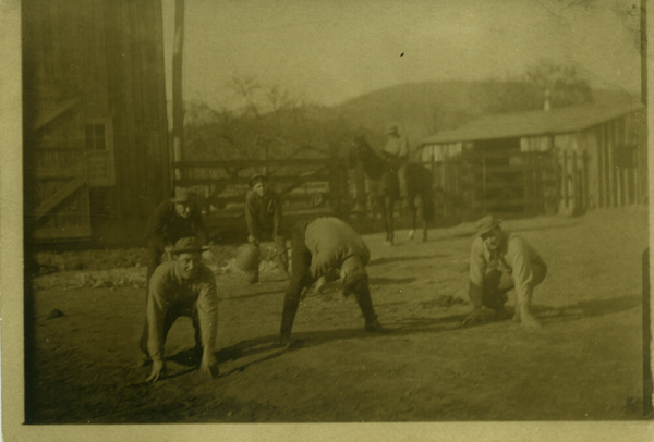 Real photo postcard of men in a barnyard playing football. Football.