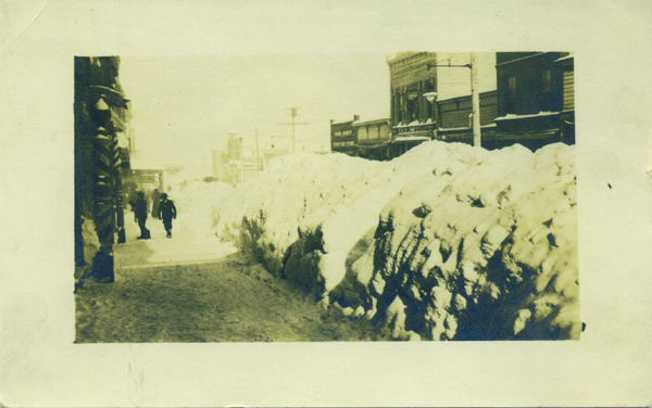 Real photo postcard view of the sidewalk of Main Street in Park City, Utah, flanked the length of the sidewalk by snow piled higher than a man's head. Photography, Utah.