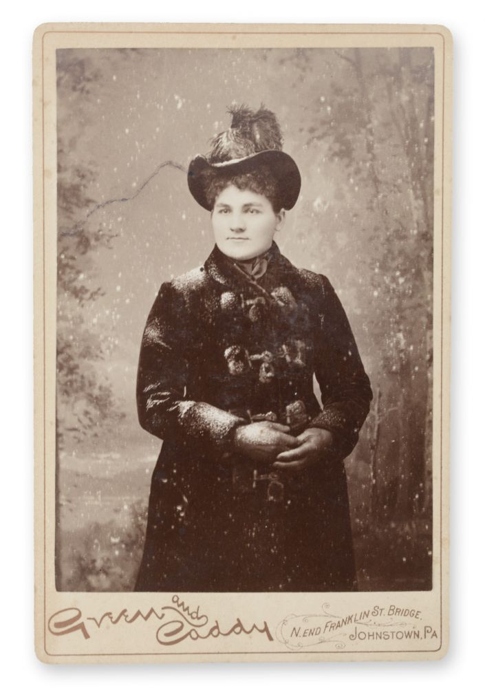 Cabinet photo studio portrait of a woman (attributed in later pencil autograph on the verso as Ella Gertrude McKee (Potter)), posing in a heavy coat amid artificial snow. Snow, Green and Caddy.