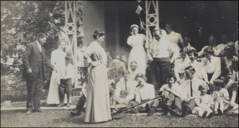 Real photo postcard image of a presumed family of nearly 30 people assembling on a porch for a group portrait; two women are seen among the group laughing with evident abandon. Laughter.