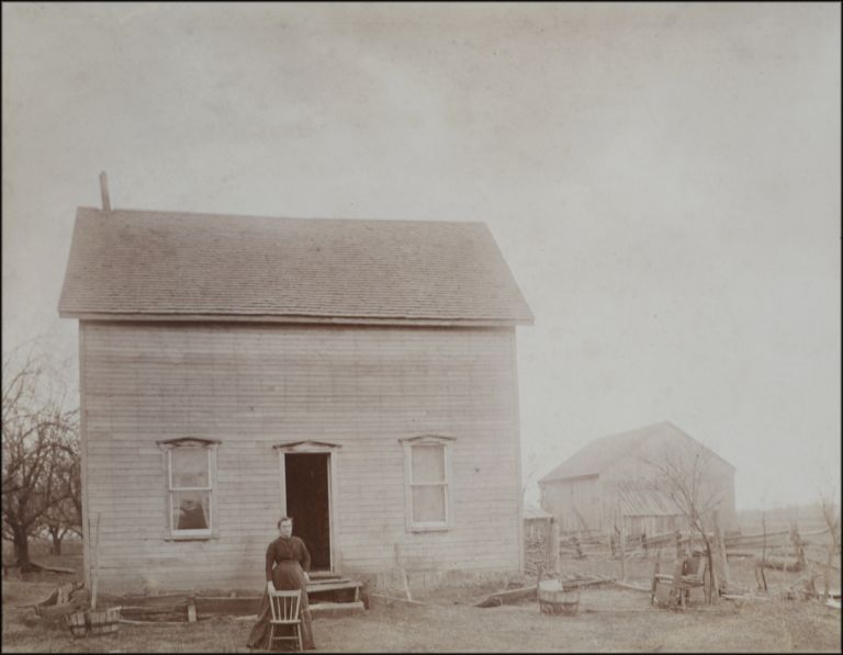 Distant outdoor portrait of a woman standing with a chair in front of a farmhouse. Chair Portraits.