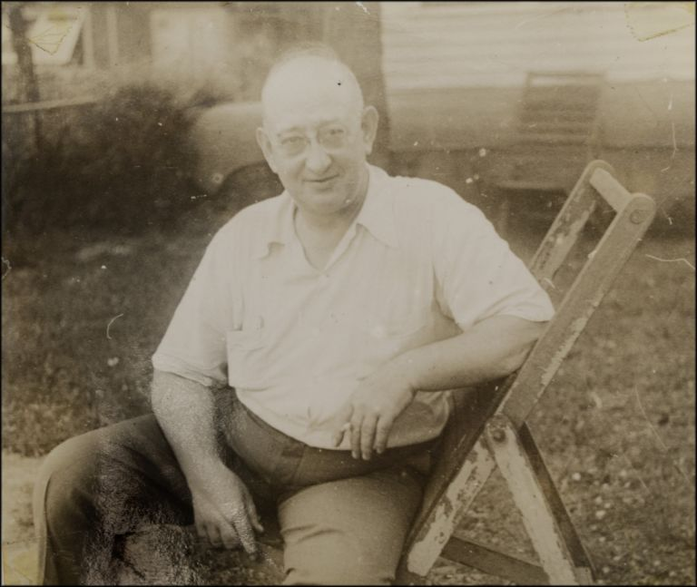 Black and white snapshot portrait of a man seated on a folding chair in a yard. American Leisure.