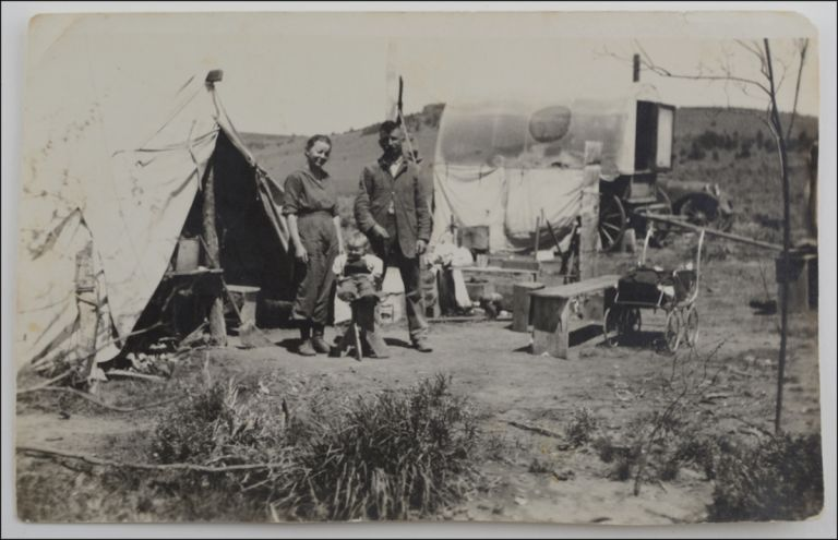 """Snapshot portrait of a man and a woman and a young child at a rough camp, annotated on the verso in contemporary ink autograph, """"Pete, Dolly, and Marie at the Sheep Camp on Willow Creek."""". Sheep Camp."""