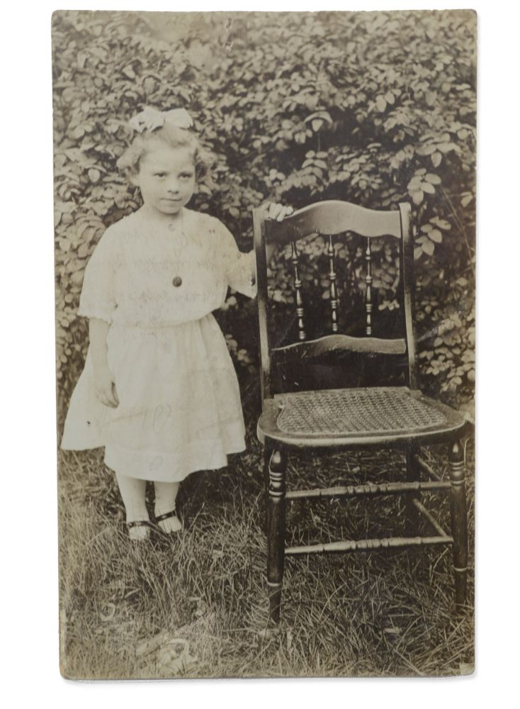 Real photo postcard portrait of a young girl posed outside beside a cane bottom chair. Portraits, Chairs.
