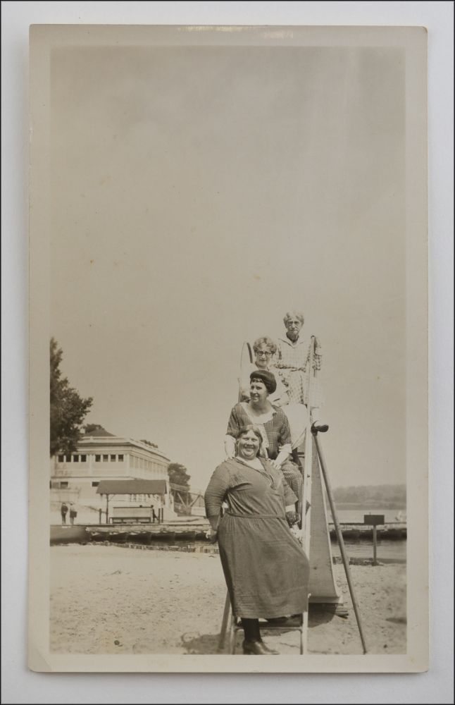 Snapshot of four older women in bathing costumes posing on the ladder of a playground slide on a beach. American Leisure.