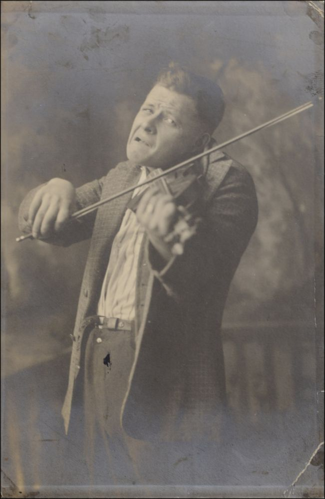 Studio portrait photograph of a performer hamming it up on violin. Love in Bloom.