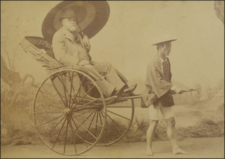 Cabinet photo studio portrait of a Western tourist seated in a rickshaw and pictured with an Asian man posing as the rickshaw runner. Japan, Kozaburo Tamamura.