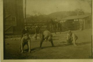 Real photo postcard of men in a barnyard playing football. Football