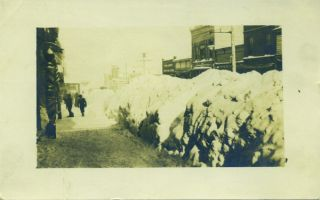 Real photo postcard view of the sidewalk of Main Street in Park City, Utah, flanked the length of...