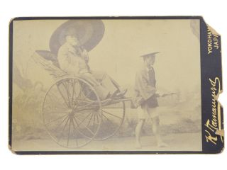 Studio cabinet photo portrait of an unidentified western man sitting in a rickshaw with a...
