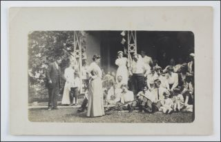 Real photo postcard image of a presumed family of nearly 30 people assembling on a porch for a group portrait; two women are seen among the group laughing with evident abandon.