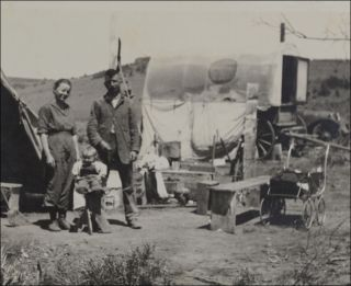 """Snapshot portrait of a man and a woman and a young child at a rough camp, annotated on the verso in contemporary ink autograph, """"Pete, Dolly, and Marie at the Sheep Camp on Willow Creek."""""""
