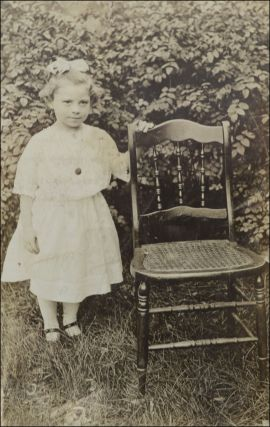 Real photo postcard portrait of a young girl posed outside beside a cane bottom chair.