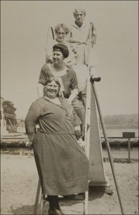 Snapshot of four older women in bathing costumes posing on the ladder of a playground slide on a beach.