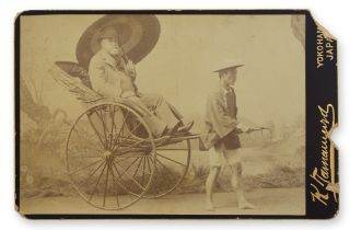 Cabinet photo studio portrait of a Western tourist seated in a rickshaw and pictured with an Asian man posing as the rickshaw runner.