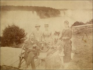 Early portrait of five tourists posed on the Canadian side in front of Niagara Falls.